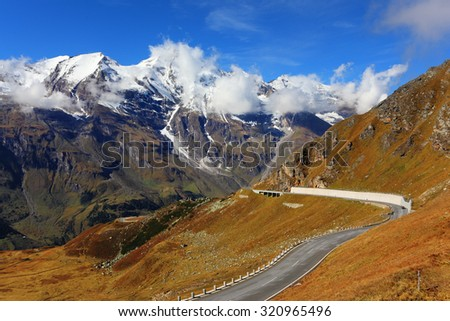 Famous picturesque views of the road in Austrian Alps - Grossglocknershtrasse. Ideal highway winds high in the mountains. The highest mountain peaks covered with fresh snow - stock photo