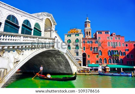 Famous Ponte di Rialto with traditional Gondola under the bridge in Venice, Italy - stock photo