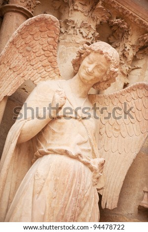 Famous smiling angel on facade of Reims Cathedral - stock photo