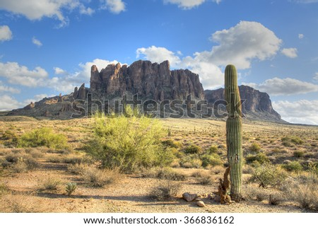 Famous Superstition Mountain in Arizona framed by a lone saguaro cactus shows the beauty of this dry desert landscape. - stock photo