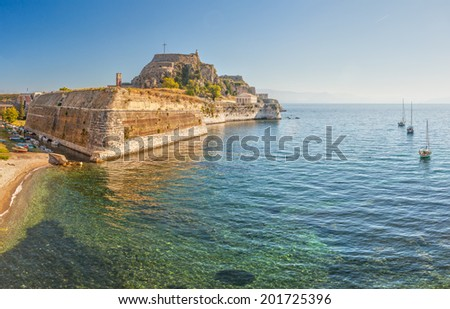 Famous touristic landmark old venetian fortress with walls going to sea and clock tower in the morning, located at Kerkyra city, Corfu, Greece
