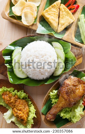 Famous traditional Indonesian food. Delicious nasi ayam penyet with sambal belacan. Fried chicken rice and tea with overhead view. - stock photo