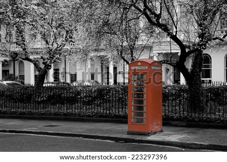 Famous, typical red british telephone booth under a tree blossoming in spring in a street with victorian houses in London, capital of the UK - stock photo