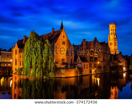 Famous view of Bruges-  Belfry and old houses along canal with tree. Brugge, Belgium - stock photo
