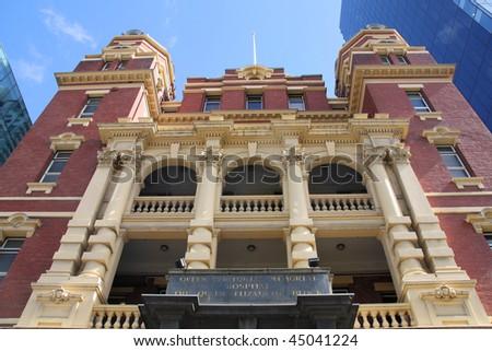 Famous vintage Queen Victoria Memorial Hospital in Melbourne, Australia. Skyscrapers in background. - stock photo