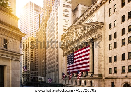 Famous Wall street and the building in New York, New York Stock Exchange with patriot flag