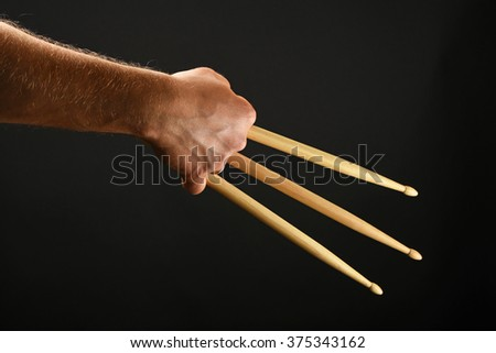 Famous wolverine claws heroic gesture, man hand holding three wooden drumsticks over black background, back view, horizontal - stock photo