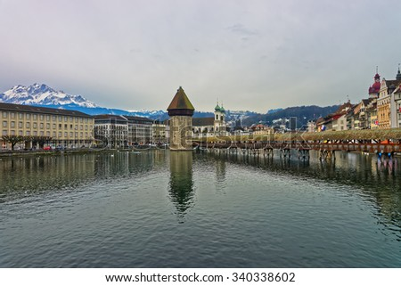 Famous wooden Chapel Bridge or Kapellbrucke in Lucerne, Switzerland, with its water tower seen in the middle. Subsequently restored, the Kapellbrucke is the oldest wooden covered bridge in Europe - stock photo