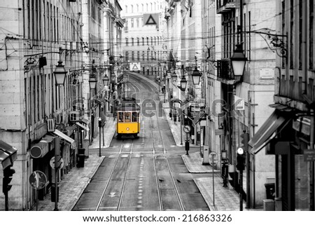 Famous yellow tram in the streets of Lisbon, capital of Portugal in the early morning with no people yet around in the center of the city - stock photo