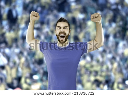 Fan in blue and white t-shirt celebrates in the stadium