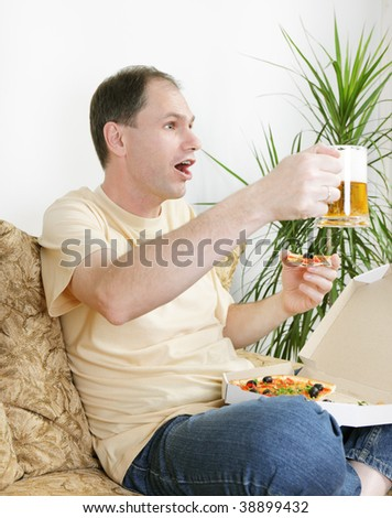 Fan on a sofa with beer and pizza