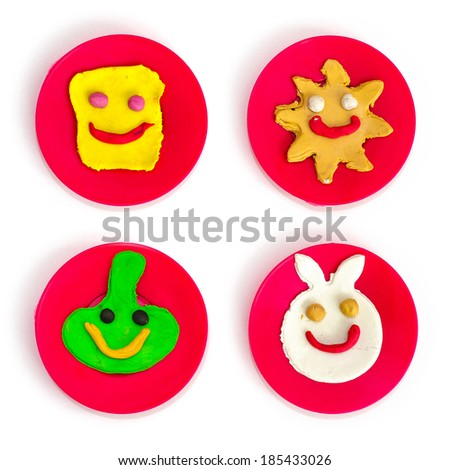 Fancy and colorful children modeled clay smiley character faces - sun, bunny, cheese and green face on red round plates - stock photo