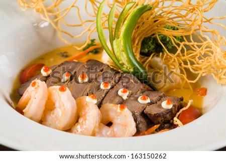 Fancy Asian shrimp and filet mignon served with crispy noodles and vegetables on a white plate. - stock photo