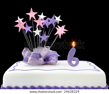 Fancy cake with number 6 candle.  Decorated with ribbons and star-shapes, in pastel tones over black background. - stock photo
