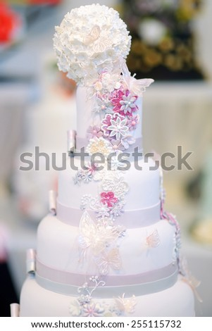 Fancy delicious white wedding cake decorated with flowers and butterflies - stock photo