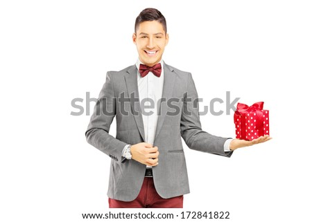 Fancy dressed young man holding a present isolated on white background - stock photo