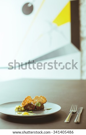 Fancy food on the plate in modern restaurant - stock photo