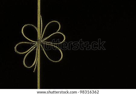 Fancy gold yellow ribbon bow isolated on black background with room for your text - stock photo
