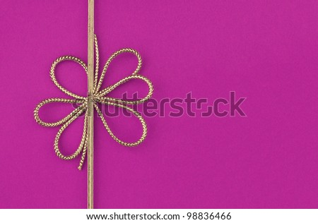 Fancy gold yellow ribbon bow isolated on purple / pink background with room for your text - stock photo