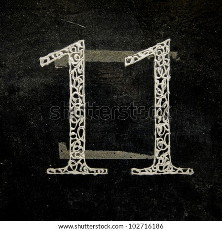 fancy house number eleven on a lacquered black background