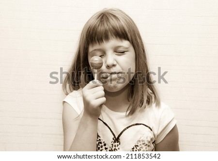 Fancy Little girl poses and lick lollypop - stock photo