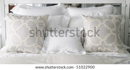 fancy pillows on the bed with mirror in the headboard - stock photo