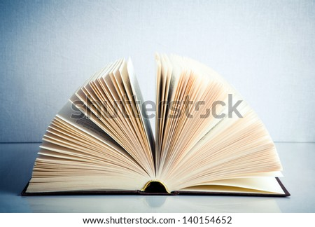 Fanned book on a white reflective surface