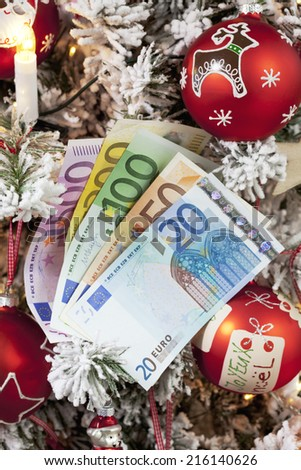 Fanned euro notes close up christmas tree in background - stock photo