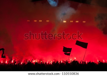 Fans burn red flares at rock concert - stock photo
