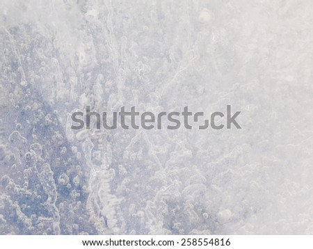 fantastic abstraction beautiful rough crystal translucent blue ice surface with fragile bubbles of air - stock photo