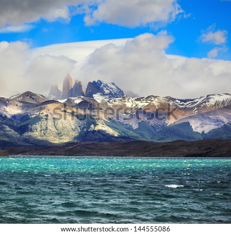 Fantastic beauty of the national park Torres del Paine in Chilean Patagonia. Strong wind drives wave in Laguna Azul emerald water. On the horizon are seen the famous cliffs of Torres - stock photo