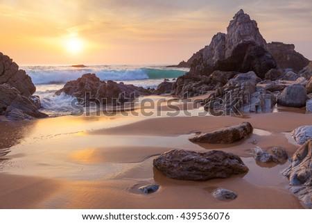 Fantastic big rocks and ocean waves at golden sundown time, Portugal - stock photo