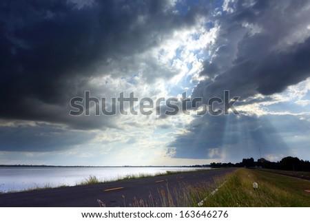 fantastic dramatic sunbeam over asphalt road - stock photo