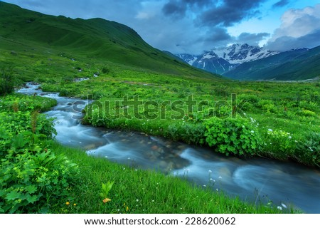 Fantastic landscape with green summer valley and blue river on Caucasus mountains. Upper Svaneti, Georgia, Europe. - stock photo