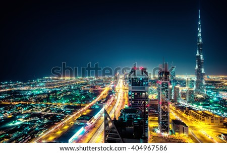 Fantastic nighttime Dubai skyline with illuminated skyscrapers. Rooftop perspective of downtown Dubai, UAE. - stock photo