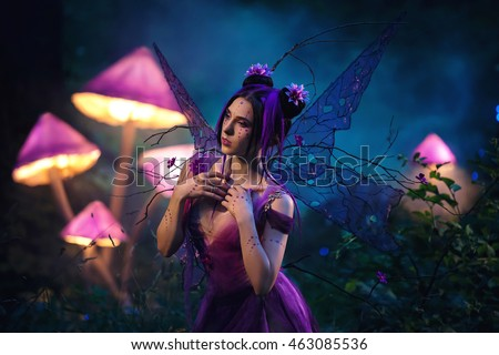 Fantastic photo shoot.  Fairy Coquette standing near the huge mushroom. Background fairy forest, scenery shine. The unusual fairy-tale image, purple dress and torn wings. Fashionable toning.