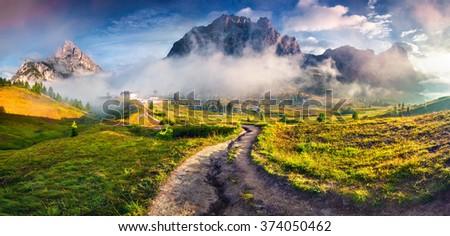 Fantastic summer scene on the Tofane mountain range. View from Falzarego pass. Foggy sunrise in Dolomite Alps, Italy, Europe. - stock photo