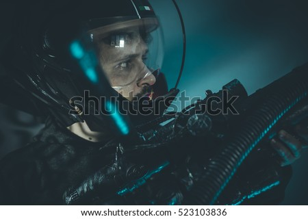 Fantasy and science fiction scene, space man with metallic helmet and laser beam weapon