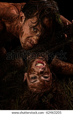 Fantasy character portrait of couple in mud over black. - stock photo