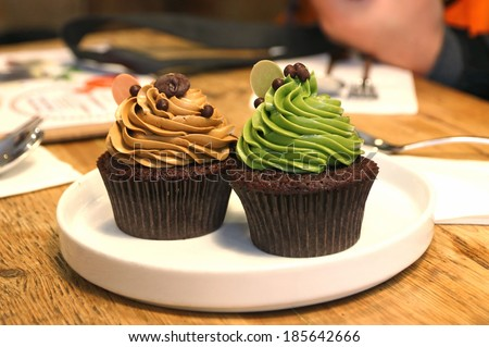 Fantasy chocolate cupcakes topping with green tea and coffee cream - stock photo