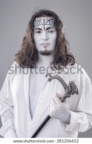 Fantasy Illusionist Performer. Body painted performer in black and white suit with hat and stick  - stock photo