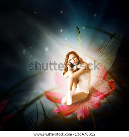 Fantasy. Magical young glowing woman as fairy firefly with wings sitting on flower in moon light - stock photo