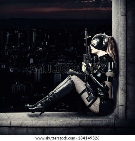 Fantasy. Military sexy woman sniper  in latex cat suit holding gun and automatic - stock photo