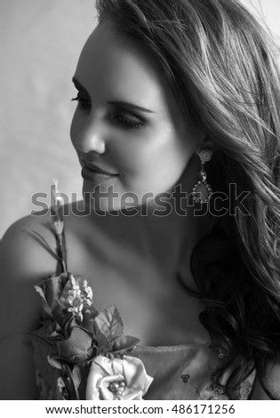 Fantasy portrait of beautiful woman wearing a dress made of flowers, earrings and her long hair in a loose style, posing with a soft smile on her lips