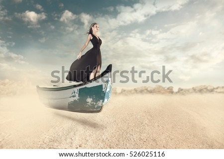 Fantasy portrait of young woman flying over sand on the boat