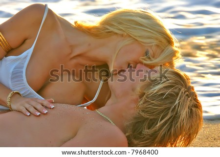 Fantasy shot of a couple kissing on the Beach in the water at Sunset.