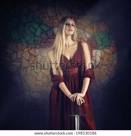 Fantasy style portrait of a woman in medieval dress with the sword looking at camera - stock photo