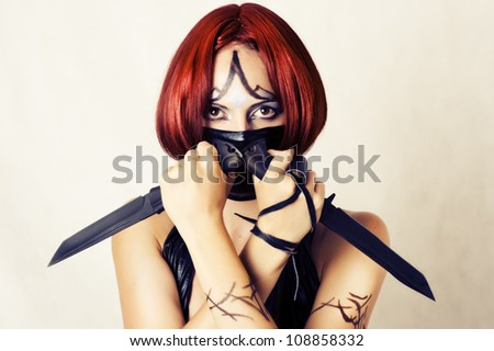 Fantasy style - red haired woman with dark creative make up, mask on her face and two combat knifes - stock photo