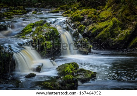 fantasy water rapid surrounded with stones covered with moss - stock photo