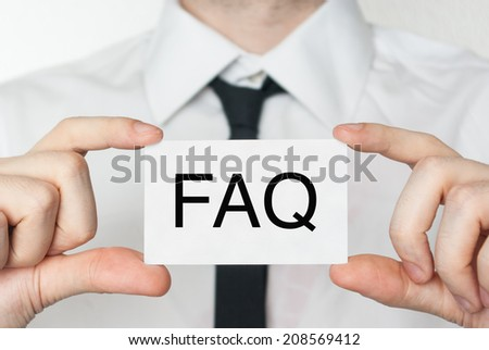 FAQ. Businessman in white shirt with a black tie showing or holding business card  - stock photo